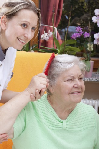 Pflegekraft leitet Seniorin zur aktivierenden Pflege an