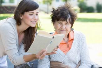 Junge Frau liest Seniorin etwas vor